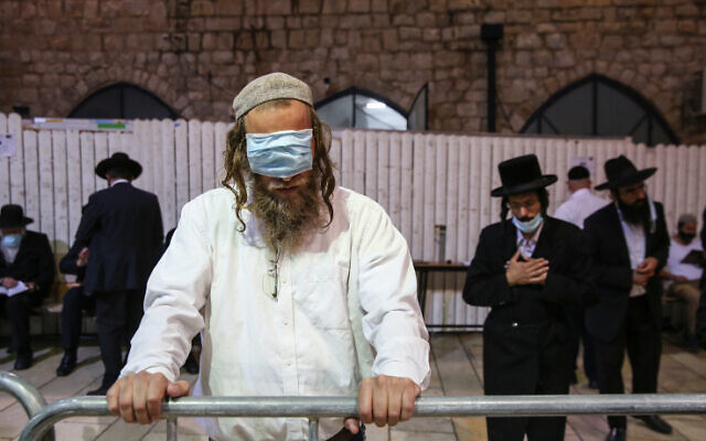 A man uses a mask as a blindfold at the burial site of Rabbi Shimon bar Yohai in Mount Meron on July 7, 2020. (David Cohen/Flash90)