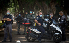 Police stand guard at a protest by self-employed Israelis protesting the lack of financial support from the government, on Rothschild Boulevard in Tel Aviv, July 7, 2020. (Miriam Alster/Flash90)