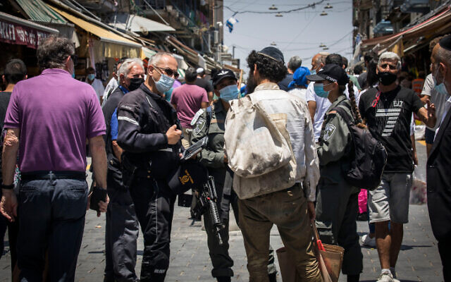 Police and shoppers at the Mahane Yehuda market  in Jerusalem on July 7, 2020. (Olivier Fitoussi/Flash90)