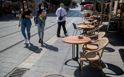 People walk next to empty chairs and tables at restaurants on Jaffa Street in Jerusalem on July 7, 2020 (Yonatan Sindel/Flash90)