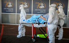 Magen David Adom paramedics in protective gear bring a patient suspected of having COVID-19 to the coronavirus unit at Sheba Medical Center at Tel Hashomer on July 8, 2020. (Flash90)