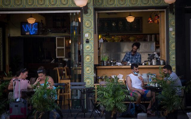 Illustrative: Israelis sit at a cafe in Tel Aviv on July 8, 2020. (Miriam Alster/Flash90)
