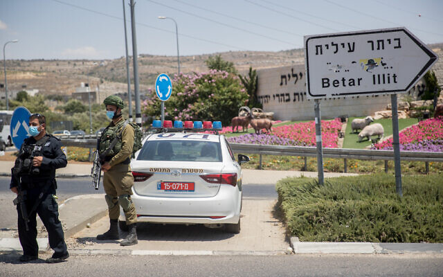 A police officer and an IDF soldier guard outside the ultra-Orthodox West Bank settlement of Beitar Illit, which is under a week-long lockdown due to a high rate of coronavirus infections, July 8, 2020. (Yonatan Sindel/Flash90)