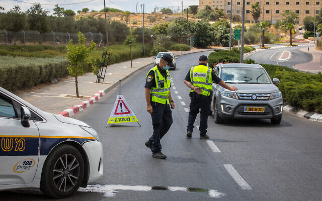 Police put up roadblocks at the ultra-Orthodox city of Beitar Illit outside of Jerusalem, which was declared a restricted zone due to a high rate of coronavirus infections, July 9, 2020. (Nati Shohat/Flash90)