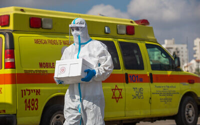 Magen David Adom medical workers test Israelis at a drive-through site to collect samples for coronavirus testing in Lod, July 10, 2020.( Yossi Aloni/Flash90)