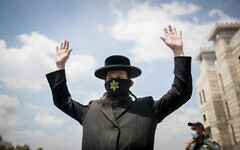 An ultra-Orthodox Jewish man wears a face mask with a yellow star on and raises his hands at a roadblock in the Hephzibah neighborhood in Beit Shemesh that is currently under a lock down in an attempt to prevent the spread of the Coronavirus, on July 10, 2020.  (Yonatan Sindel/Flash90)