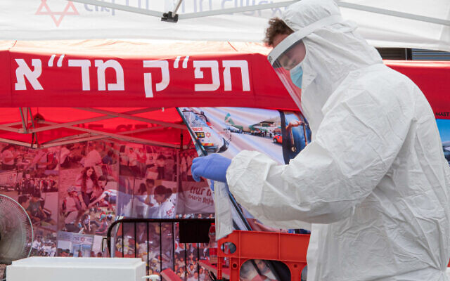 A Magen David Adom medical worker tests Israelis at a drive-through site to collect samples for coronavirus testing on July 10, 2020. (Chen Leopold/Flash90)
