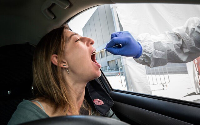 A Magen David Adom paramedic tests a woman at a drive-thru coronavirus testing site on July 11, 2020. (Chen Leopold/Flash90)