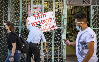 A man hangs a 'for rent' sign on a store in Jerusalem on July 12, 2020. (Olivier Fitoussi/Flash90)