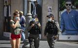 Jerusalem residents wearing face masks for fear of coronavirus  walk on Jaffa Road in the city center of Jerusalem on July 12, 2020. (Olivier Fitoussi/Flash90)