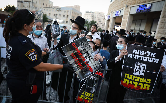 Ultra-Orthodox Jewish men and youths seen during a protest against the closure on the Romema and Kiryat Belz neighborhoods in Jerusalem that is currently under a lock down in an attempt to prevent the spread of the coronavirus, on July 12, 2020. (Olivier Fitoussi/Flash90)