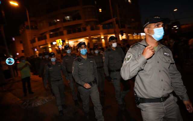 Border police officers guard during a protest against the closure on the Romema and Kiryat Belz neighborhoods in Jerusalem that is currently under a lock down in an attempt to prevent the spread of the coronavirus, on July 12, 2020. (Olivier Fitoussi/Flash90)