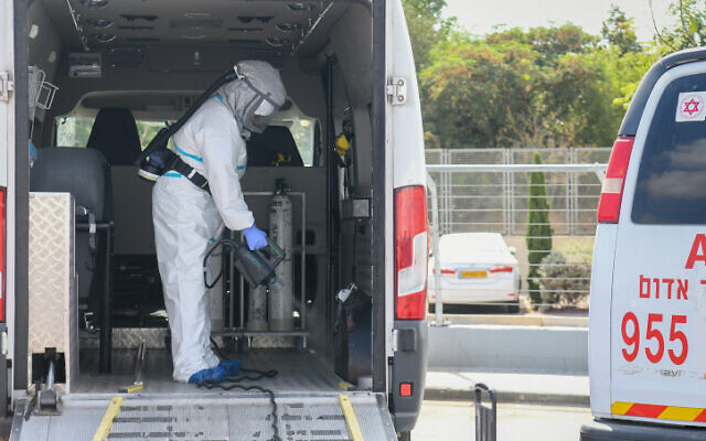 A worker disinfects a car outside the Sheba Medical Center in Ramat Gan on July 13, 2020 (Yossi Zeliger/Flash90)