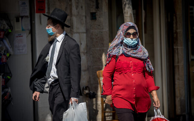 People wearing face masks, due to the coronavirus outbreak, on Jaffa Street in downtown Jerusalem on July 13, 2020. (Yonatan Sindel/Flash90)