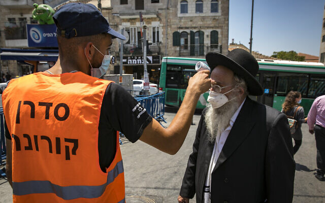 An inspector checks the temperature of an ultra-Orthodox Jewish man at the entrance to Jerusalem's Mahane Yehuda market on July 14, 2020. (Olivier Fitoussi/Flash90)