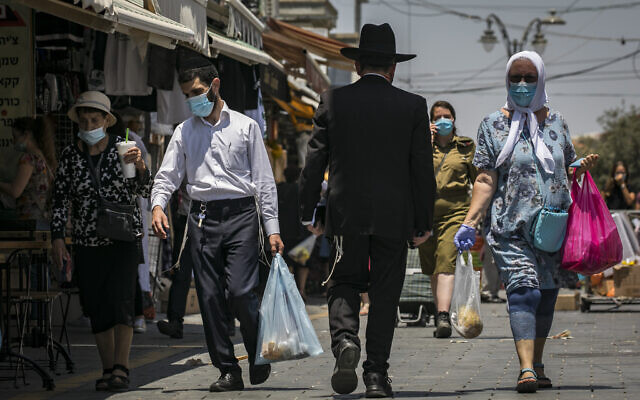 People wearing face masks shop for groceries at the Mahane Yehuda market in Jerusalem, on July 14, 2020. (Olivier Fitoussi/Flash90)