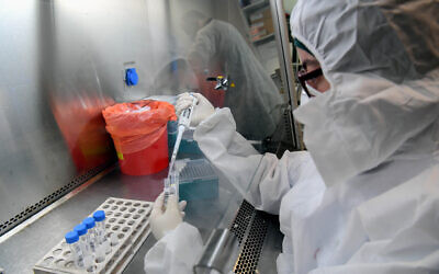 Technicians carry out a diagnostic test for coronavirus in a lab at Leumit Health Care Services branch in Or Yehuda, on July 14, 2020 (Yossi Zeliger/Flash90)