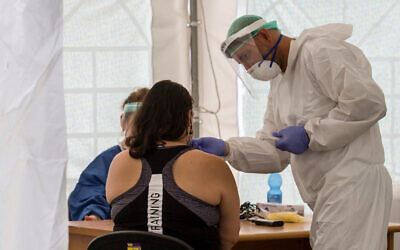 Illustrative: Medical workers test local residents at a temporary site to collect samples for coronavirus, in south Tel Aviv on July 16, 2020.(Flash90)