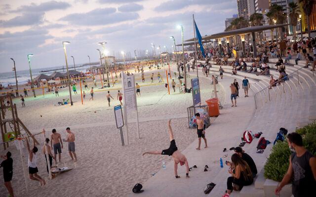 People enjoy the beach in Tel Aviv on July 18, 2020. (Miriam Alster/Flash90)