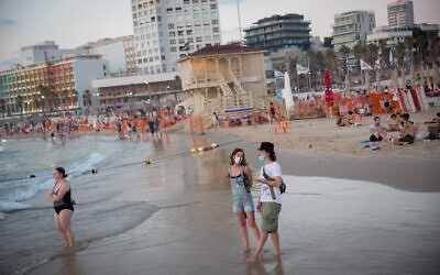 People wearing face masks due to the coronavirus outbreak enjoy the beach in Tel Aviv on July 18, 2020. (Miriam Alster/Flash90)