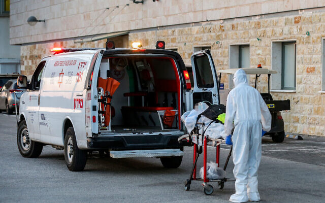 A Magen David Adom paramedic wearing protective clothing evacuates a patient with COVID-19, outside the coronavirus unit at Ziv Medical Center in Safed, July 19, 2020. (David Cohen/Flash90)