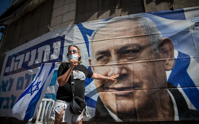 A supporter of Prime Minister Benjamin Netanyahu protests outside the Jerusalem District Court during a hearing in his trial on July 19, 2020 (Yonatan Sindel/Flash90)