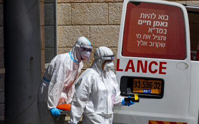 Magen David Adom ambulance crew wearing protective clothing after delivering a man suspected of infection with the coronavirus to  Hadassah Ein Kerem Medical Center, in Jerusalem, on July 20, 2020.(Olivier Fitoussi/Flash90)