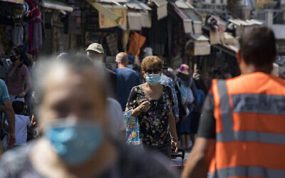 Israelis, wearing face masks to protect from the coronavirus, shop at the Mahane Yehuda market in Jerusalem on July 21, 2020 (Olivier Fitoussi/Flash90)