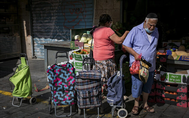 People wearing face masks due to the coronavirus outbreak shop for groceries at the Mahane Yehuda market in Jerusalem on July 21, 2020. (Olivier Fitoussi/Flash90)