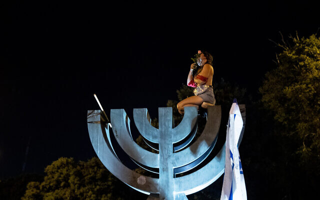 A topless protester sits on a menorah statue near the Knesset during a demonstration against Prime Minister Benjamin Netanyahu in Jerusalem on July 21, 2020. (Yonatan Sindel/Flash90)