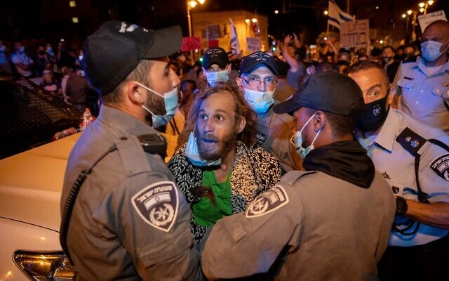 Police officers detain a man during a protest against Prime Minister Benjamin Netanyahu outside his official residence in Jerusalem on July 21, 2020. (Yonatan Sindel/Flash90)