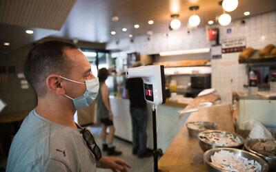 A man checks his body temperature as he enters a coffee shop in Jerusalem on July 21, 2020 (Yonatan Sindel/Flash90)