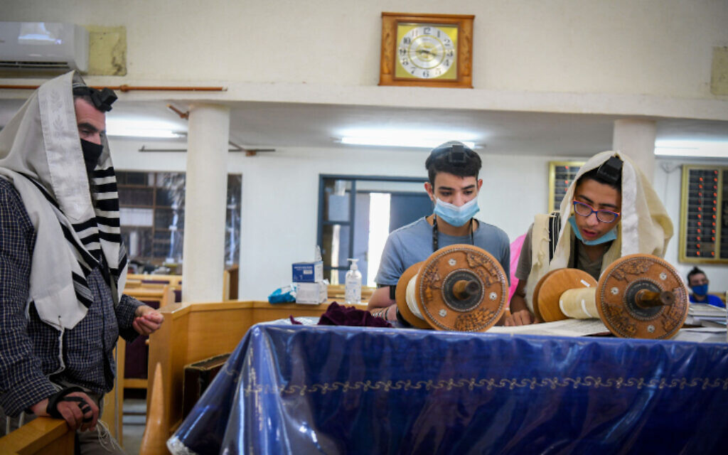 Illustrative: People pray with masks at a synagogue in Moshav Tzafria, on July 22, 2020 (Yossi Zeliger/Flash90)