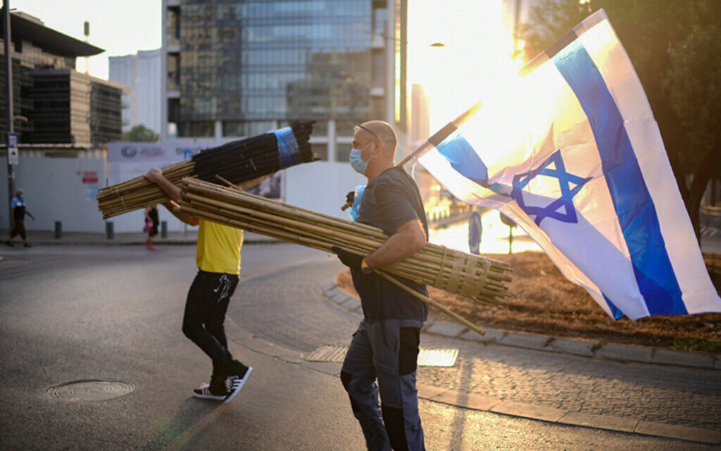 A protester carrying an Israeli flag near the home of Public Security Minister Amir Ohana on July 28, 2020 in Tel Aviv. (Tomer Neuberg/Flash90)