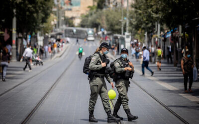 Border police officers enforce the coronavirus regulations on Jaffa Street in downtown Jerusalem on July 28, 2020. (Yonatan Sindel/Flash90)