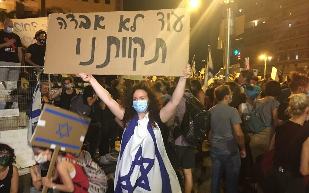 "Israelis protest against Prime Minister Benjamin Netanyahu outside his official residence in Jerusalem on July 25, 2020. The sign in foreground, quoting from the Hatikvah national anthem, reads ""Our hope is not yet lost"" (Aaron Boxerman/Times of Israel)"
