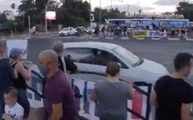 Screen capture from video of a driver allegedly spraying pepper spray from the window of a car at protesters against Prime Minister Benjamin Netanyahu at the Aluf Sadeh Junction, July 25, 2020. (Twitter)