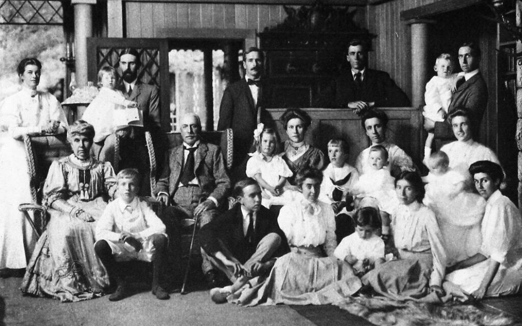 Parents of Graham Stokes (seated, left and center) with their children, children-in-law, and grandchildren at their Adirondack estate in 1907. Graham is standing, hands crossed on counter; Rose Pastor Stokes is on floor, second from right. (Stokes Records, vol. 3, by Anson Phelps Stokes)