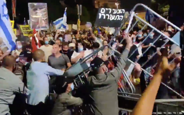 Demonstrators try to break through barriers during a protest against Prime Minister Benjamin Netanyahu outside the PM's residence in Jerusalem, July 14, 2020. (Twitter screenshot)