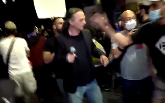 Anti-Netanyahu protesters attack Channel 13 journalist Avishay Ben Haim as he covers a protest calling for the premier's ouster outside of his Jerusalem residence on July 14, 2020. (Screen capture/Twitter)