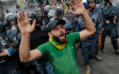 A Hezbollah supporter shouts slogans in front of riot police during a protest against the US near its embassy in Aukar, northeast of Beirut, Lebanon, July 10, 2020. (AP Photo/Hussein Malla)