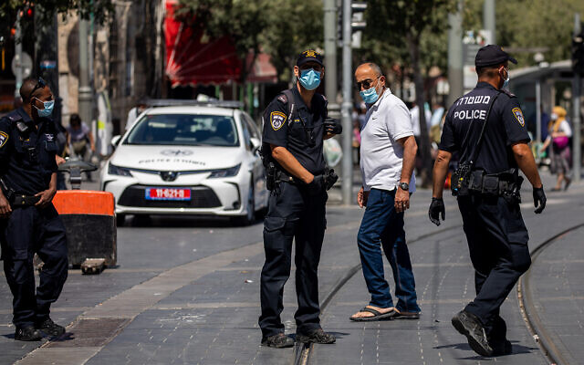 Police officers patrol outside the Mahane Yehuda Market in Jerusalem to enforce emergency COVID-19 regulations, on July 3, 2020. (Yonatan Sindel/Flash90)