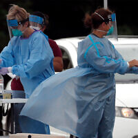 Medical personnel assist patients at a community coronavirus testing site operated in Burlington, North Carolina, July 9, 2020. (AP Photo/Gerry Broome)