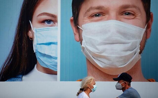 People wearing protective face masks pass a billboard in Ramat Gan, near Tel Aviv, July 16, 2020. (AP Photo/Oded Balilty)
