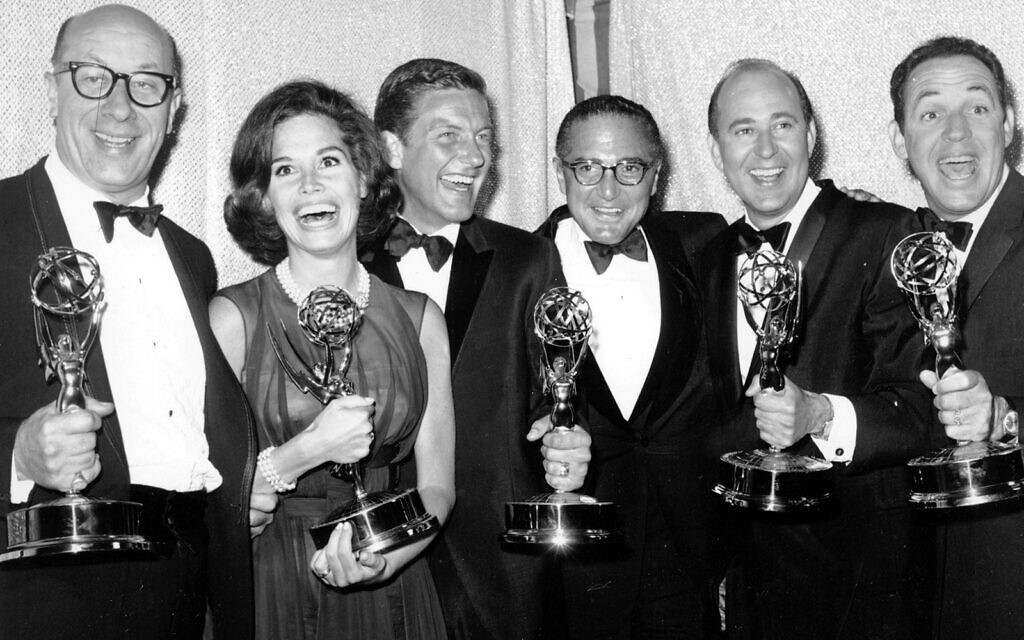 """Cast and crew of the television comedy series """"The Dick Van Dyke Show"""" from left, Richard Deacon, Mary Tyler Moore, Outstanding Continued Performance by an Actress in a Series, Lead; Dick Van Dyke, Outstanding Continued Performance by an Actor in a Series, Lead; Sheldon Leonard, producer of the show, which was named best comedy series; Carl Reiner, Outstanding Writing Achievement in a Series; and Jerry Paris, Outstanding Directorial Achievement in Comedy. pose with their awards at the 16th Annual Emmy Awards in Los Angeles, May 24, 1964. (AP Photo, File)"""