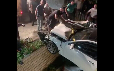 First responders lift a vehicle out of a yard in Ar'ara, northern Israel, July 30, 2020 (Kan screenshot)