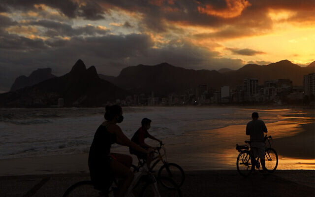 Cyclists wear face masks on Ipanema beach in Rio de Janeiro, Brazil, July 2, 2020. (Carl de Souza/AFP)