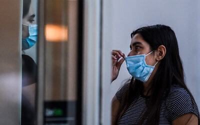 A woman wears a face mask as she talks to a friend at a shopping center in Miami Beach, Florida, June 29, 2020. (Chandan Khanna/AFP)