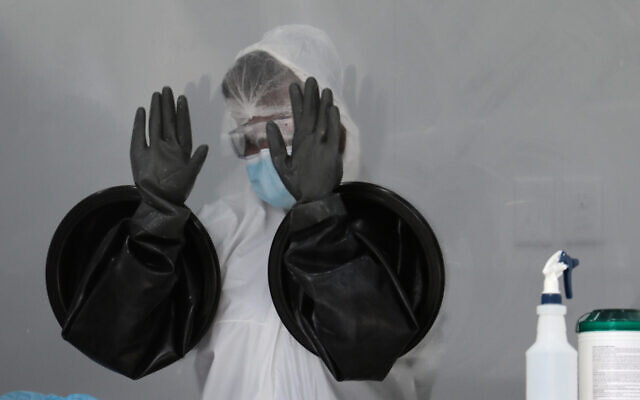 A health care worker air dries her gloves after sanitizing her equipment while working at a walk-up COVID-19 testing site in Miami Beach, Florida, July 17, 2020. (AP Photo/Lynne Sladky)