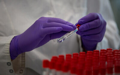 Illustrative: A lab technician puts a label on to a test tube while conducting research on coronavirus in Beerse, Belgium, June 17, 2020. (AP Photo/Virginia Mayo)